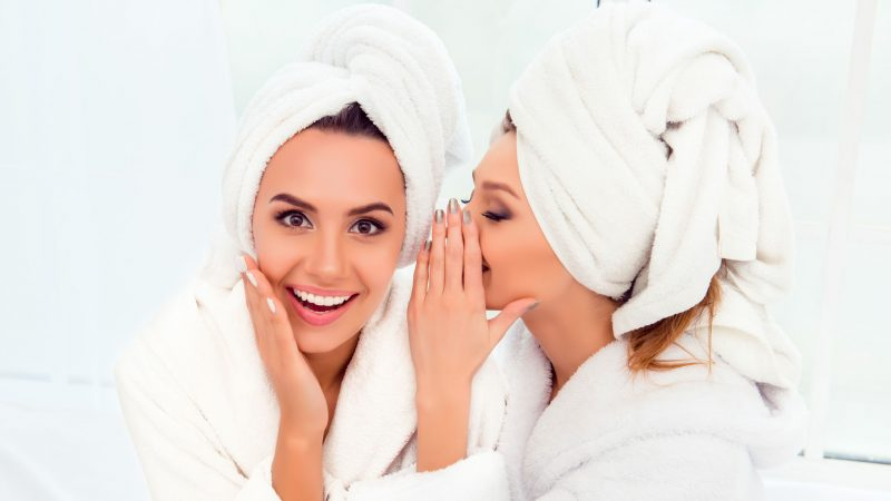 Girl in bathrobe and towel on her head telling secret to her sister